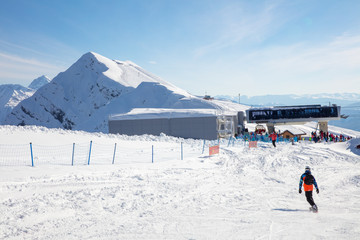skiers and snowboarders on the ski slope on background peak of mountain