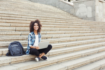 Smiling student sitting on stairs using laptop