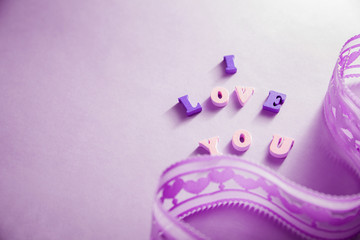 I love you lettering with a ribbon on purple background. Valentine's day concept.