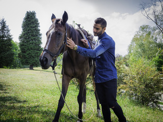 Handsome man standing and stroking horse in natural bright sunlight.