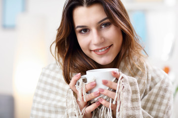 Adult woman covered with blanket having flu