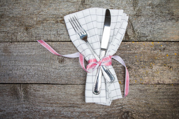 Festive table setting. Knife and fork on white napkin. Valentine's Day