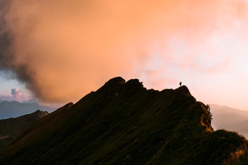 Sunset in the Algau region of Germany- mountain ridge with hiker during golden hour with dramatic orange clouds