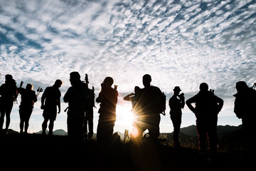 Sunrise in the Algau region of Germany- group of young adult hikers standing on a mountain during golden hour  with dramatic sky