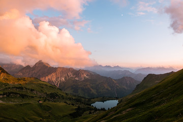 Sunset in the Algau region of Germany- mountain lake and ridge during golden hour with dramatic orange clouds