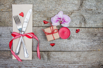 Cutlery, orchid flower and candle on wooden table. Valentine's Day