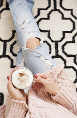 A young woman wearing distressed jeans sitting on wood floor on a rug carpet at home and holding a cup of coffee in hands