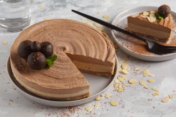 Raw vegan chocolate-caramel cheesecake with raw balls. Healthy vegan food concept.