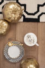 Cappuccino and gold pumpkins on wooden floor. Stripe design