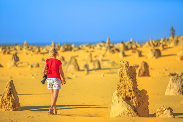 Western Australia travel discovery concept. Traveler woman photographer walks through Pinnacles Desert, Nambung National Park, Cervantes. Female with professional camera among limestone formations, WA