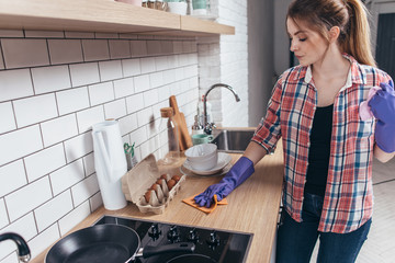Woman in rubber gloves cleaning kitchen table.