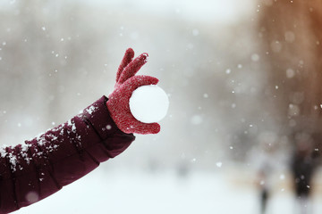 Close up of woman holding the snowball in hands, winter concept with copy space