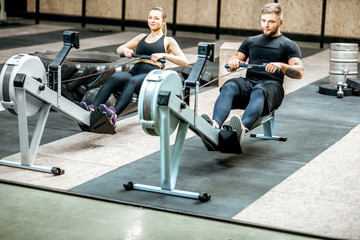 Young and beautiful couple training with exercise rowing machines in the gym