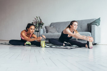 Fit women doing stretching while sitting on the floor at home