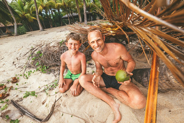 Father and son sit in selfmade hut of branches and play in Robinzones