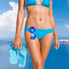 Sun beach bikini body woman with toned abs and slim legs tanning on vacation holding flip flops sandals and sunglasses accessories. Fit stomach weight loss and cellulite free thighs skin care concept.