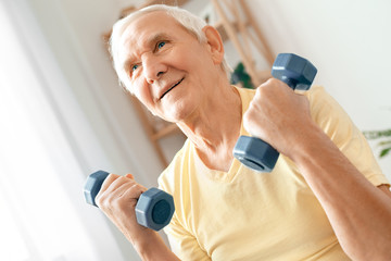 Senior man exercise at home health care sitting holding dumbbells