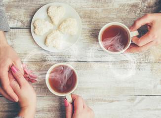 A cup of tea in the hands of a man and a woman. Selective focus.