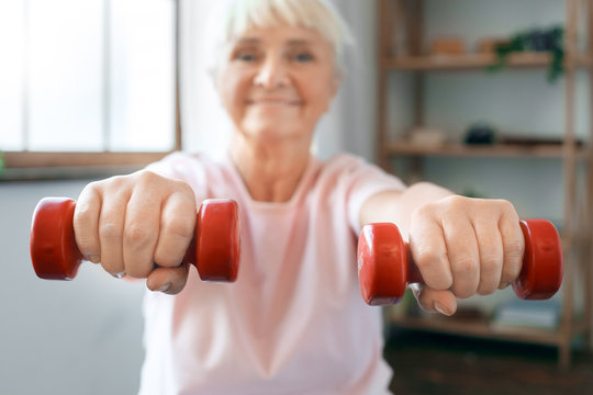 Senior woman exercise at home sitting on exercise ball with dumbbells in front blurred