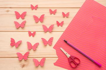 Mariposas rosas de papel y los materiales para hacerlas (papel, bolígrafo y tijeras) sobre una mesa de madera.
