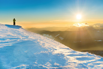 Man looking at sunset, sun and beautiful winter mountains with snow