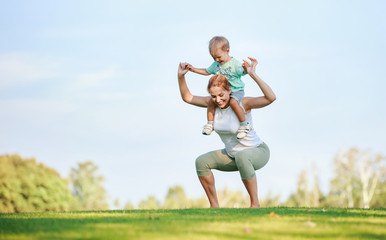 Young fitness woman working out with son on shoulders
