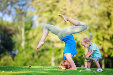 Young woman working out outdoors, little son playing beside her