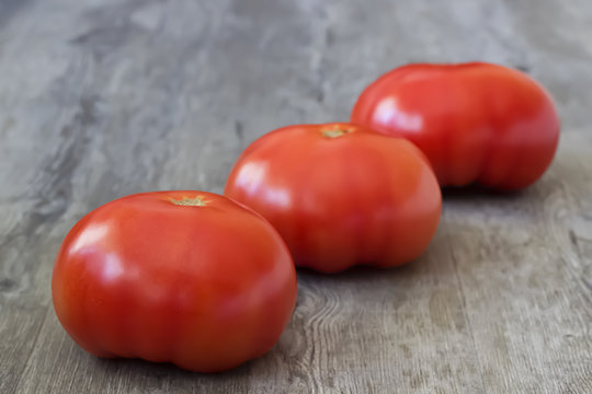 Ripe whole large tomatoes and a knife on a gray wooden background.