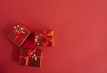 Tiny red gift boxes over red background. Valentones day background