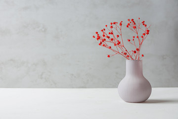 Small Bouquet of Red Flowers in Vintage Vase on White Table Grey Cement Wall Background. Styled Stock Image Mockup for Text Artwork Quotes Lettering Website Banner Template. Easter Mother's Day