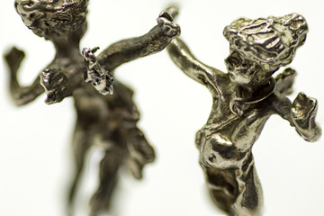 two metallic figurine angels are dancing