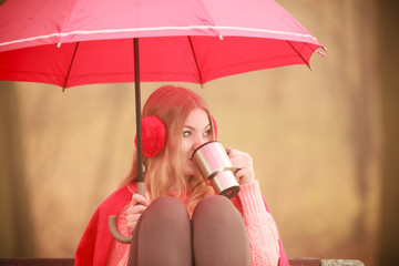 Girl sitting in park with umbrella