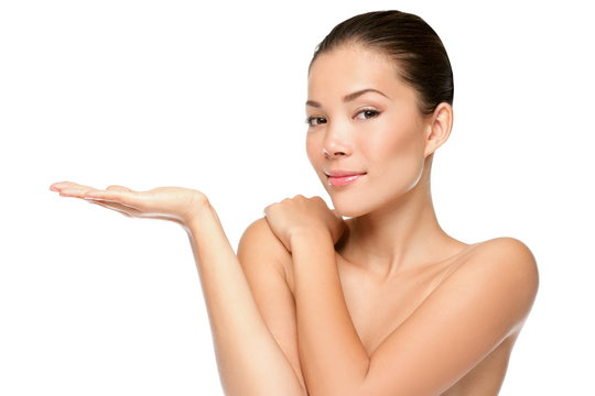 Beauty portrait of beautiful woman showing beauty product / empty copy space on open hand palm. Mixed race Asian / Caucasian female model isolated on white background.