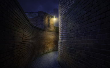 Curved pathway among old red brick walls at night. The street lamp illuminates the turn of the path to the right