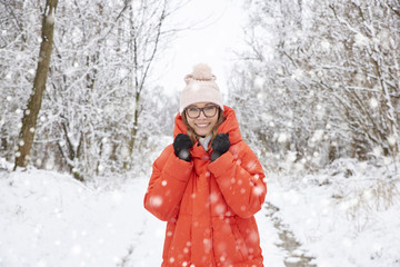 Woman in snowfall. Close-up portrait shot of a happy middle aged female wearing hat while standing outdoor and enjoy snowfall.
