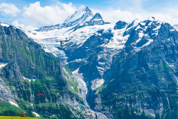 Impressing mountain chains. Parachuter. Jungfrau-Aletsch-Bietschhorn UNESCO World Natural Heritagei n summer. Skydivers and tourists.