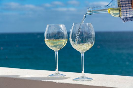Waiter pouring glass of white wine on outdoor terrace with sea view