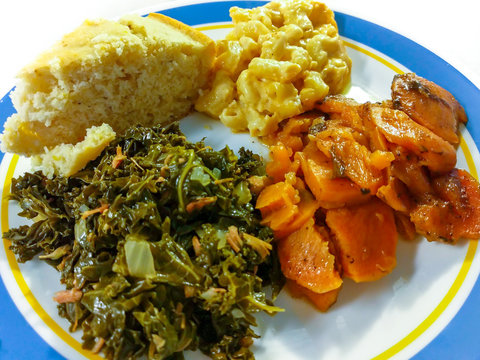 Comfort food in America. Close up serving of kale greens, candied yams, macaroni and cheese, and cornbread served on a white and blue plate.