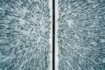 blue car drive along the road through the winter forest. Road seen from the air. Aerial view landscape. Drone photography