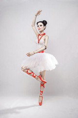 girl as a doll in a ballerina costume with red ribbons on a white background