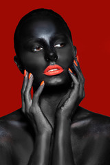 girl with black skin and red lips and nails on a red background