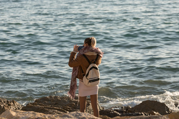 Blonde girl in the bag photographing the sea with her mobile phone