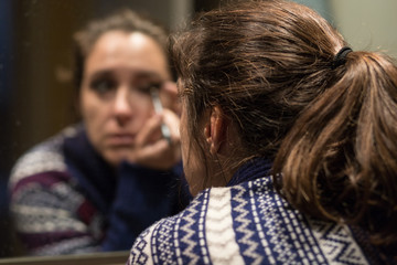 Woman making up in front of the mirror with the image of her face blurred