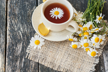 cup of herbal chamomile tea with fresh daisy flowers on wooden background. doctor treatment and prevention of immune concept, medicine - folk, alternative, complementary, traditional medicine