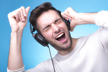Sexy young man listening to his favorite music through his headphones jacked in cell phone