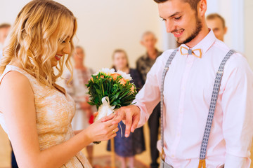 Close-up of newlyweds who are standing at a festive ceremony and exchanging weddings rings and behind them are relatives