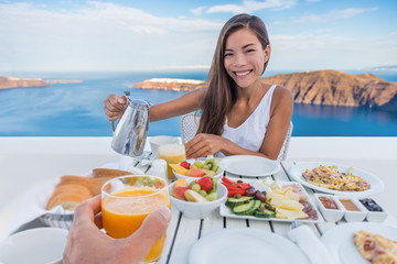 Couple eating breakfast at luxury resort - honeymoon Europe travel vacation, Santorini, Greece. Asian woman drinking coffee on outdoor hotel restaurant, Mediterranean sea view. Healthy food brunch.