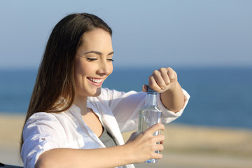 Girl opeining a water bottle on the beach