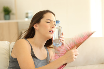 Girl suffering a heatstroke refreshing with a fan