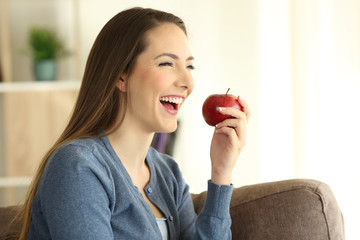 Happy woman eating an apple looking away